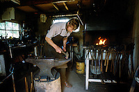 Blacksmith Hector Cole working with anvil and furnace in traditional forge in Gloucestershire, UK