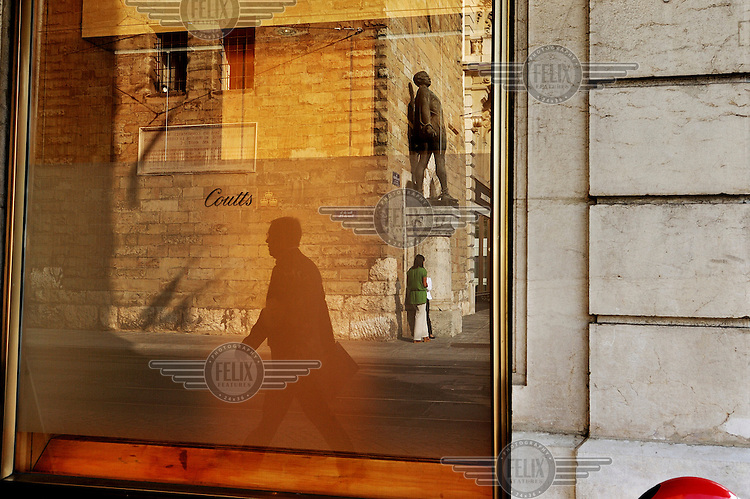 A man is reflected in the window of British bank Coutts.