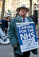 Protester - 2011<br /> <br /> London, 23/03/2011. UK Prime Minister David Cameron leaves 10 Downing Street on Budget Day. He is followed by  the Chancellor of the Exchequer, George Osborne, who (followed by his team) shows the &quot;red box&quot; (Budget Box) containing the Budget for the fiscal year. In the meanwhile, outside the gates of Downing Street, protesters gather for a variety of demonstrations. The demands of protestors included an end to the Government budget cuts and austerity measures and a stop to cuts in the NHS.