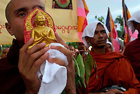 Buddhist monk holding an icon of the Buddha on a protest march calling for the overthrow of the country's military junta.