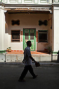 A pedestrian walks past a restored heritage house in the UNESCO heritage town - Georgetown of Penang, Malaysia. Photo: Sanjit Das/Panos