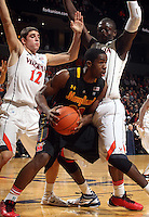 Jan. 27, 2011; Charlottesville, VA, USA; Maryland Terrapins guard/forward Cliff Tucker (24) is defended by Virginia Cavaliers guard Joe Harris (12) and Virginia Cavaliers center Assane Sene (5) during the game at the John Paul Jones Arena. Mandatory Credit: Andrew Shurtleff