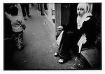 13..Young Maghrebi woman, wearing a hijab headscarf, begs with a paper McDonald?s cup in front of Tunisian shops, Belleville