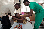 Nurse Mustafa Senesie, right, and Santigie Bundu, left, prop up his severely dehydrated 7-year-old son Alusine Bundu so that he can drink oral rehydration solution at Macaulay Cholera Treatment Center, Freetown, Sierra Leone, Aug. 13, 2012. Médecins Sans Frontières Belgium, in collaboration with the Sierra Leone Ministry of Health, is running four emergency cholera treatment centers to keep up with the number of patients. Many of the roughly 120 daily patients seen by the MSF team come from extremely impoverished areas of the densely-populated capital, where proper systems for drainage and waste disposal are almost non-existent. Outbreaks of water-borne diseases like cholera become even more likely during the rainy season, which is expected to last at least two more months.