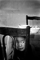 A young girl peeks through a chair at a restaurant in rural Mongolia.