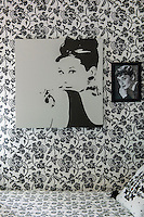 This monochrome floral bedroom is a shrine to the actress Audrey Hepburn and features a framed black and white photograph and an unframed 60s style artwork
