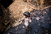 Young children dig out coal from the open cast mines and carry them back to their village in Borapahari in Jharia, Jharkhand, India.  Photo: Sanjit Das
