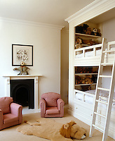 Wooden bunk beds have been built into one side of this children's bedroom which is furnished with mini armchairs and a toy lion skin rug
