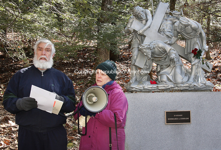 (Left) Gerry and Susan White lead dozens of Good Friday observers who gathered to celebrate the Way of the Cross service at Shrine of Lourdes in Litchfield Friday morning. Stations depicting the crucifixion and resurrection of Jesus are positioned along a paved path in the woods on the Shrine's grounds. . Michael Kabelka / Republican-American