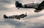 Close up of two Spitfires scrambling to takeoff at Duxford airport in Cambridgeshire, England