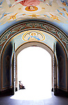 Old woman sitting behind open cathedral gates leading into the light Christian religious paintings inside the gate house Heaven's gate concept Kiev Ukraine Eastern Europe Archangel Michael cathedral entrance