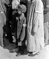 Six-year-old war orphan with Buchenwald badge on his sleeve waits for his name to be called at roll call at Buchenwald camp, Germany for departure to Switzerland.  June 19, 1945.  Pfc. G. A. Haynia. (Army)<br /> NARA FILE #:  111-SC-208199<br /> WAR &amp; CONFLICT BOOK #:  1109