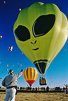 Dressed in black and white stripes, an official, known as a Zebra, signals the pilot of a hot air ballooon resembling  an alien from a UFO to take off  at the Albuquerque Internaional Hot Air balloon Fiesta