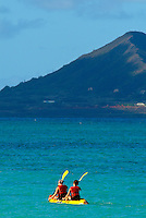 Two young women in a bright yellow kayak paddling through turquoise blue ocean, Kailua bay, Windward Oahu