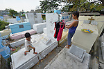 """In the capital of the Philippines, Aramay Calma (right) hangs laundry over tombs in the Manila North Cemetery, where she lives, as a small child jumps from one tomb to another. Hundreds of poor families live here, dwelling in and between the tombs and mausoleums of the city's wealthy. They are often discriminated against, and many of their children don't go to school because they're too hungry to study and they're often called """"vampires"""" by their classmates. With support from United Methodist Women, KKFI provides classroom education and meals to kids from the cemetery at a nearby United Methodist Church."""