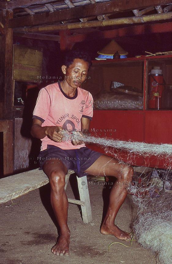 Indonesia, Java Island: a fisherman weaving fishing nets.<br /> Indonesia, isola di Giava, pescatore prepara le reti.