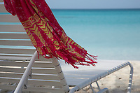 Anguilla,  British West Indies, Caribbean - A pink shawl of sarong flaps in the breeze in the side of a beach chair looking out at the turquoise water of Rendezvous bay.