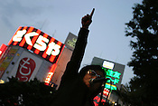 A band plays in the street as the light fades and the neon glows, Shinjuku, Tokyo, Japan.