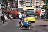 In Utrecht fietst een moeder met twee kinderen op een Gazelle bakfiets door de historische binnenstad.<br /> <br /> In Utrecht a young mother is cycling with two children on a Gazelle cargo bike at the historical center.
