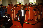 Calvary Church of God in Christ , London Uk. A member is filled with the Holy Spirit he dances joyously as he runs around the church interior, while the red robbed choir of the Calvary Church of God in Christ carry on singing.