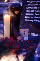 Moscow, Russia, 27/01/2011..A woman places an icon and arranges floweres at a memorial ceremony in central Moscow for the 35 people killed in the Domodedovo airport bombing.