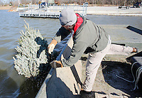 NWA Democrat-Gazette/DAVID GOTTSCHALK  Kevin Hopkins, a fisheries biologist with the Arkansas Game and Fish Commission, drops a Christmas tree Wednesday, January 13, 2016, tethered to cinder blocks  from a 22 ft. boat into Lake Elm Dale east of Springdale. Hopkins was with Jon Stein, also a fisheries biologist with the Arkansas Game and Fish Commission, dropping the donated trees into the lake as part of the Christmas Tree Habitat Program.