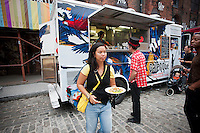 Visitors to the Dumbo Arts Festival in Brooklyn in New York on Saturday, September 24, 2011 line up to buy arepas and other Columbian food from the Palenque food truck. Numerous food vendors parked at the festival providing the hungry with a wide variety of ethnic, comfort food and snacks as they viewed the art. (© Richard B. Levine)