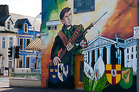 Belfast, Northern Ireland, United Kingdom, May 2011. Children pass a mural of an armed man on Beechmount avenue in the old days better known as RPG avenue, where the rocket propelled grenades flew throug the street regularly. For decades travellers stayed away from the sectarian violence, but since the end of'The Troubles' more and more people start discoving the beauty of Belfast and the Antrim Coast Causeway. Photo by Frits Meyst/Adventure4ever.com