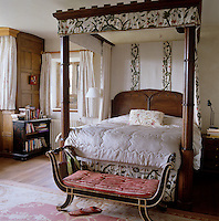 In the master bedroom a neo-gothic four-poster bed is draped with a heavily embroidered Jacobean-inspired floral fabric perfectly chiming with the architecture of the house