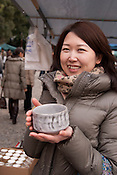 A young Japanese lady showing a green tea cup in Osu, the trendy shopping district for young people of Nagoya city.