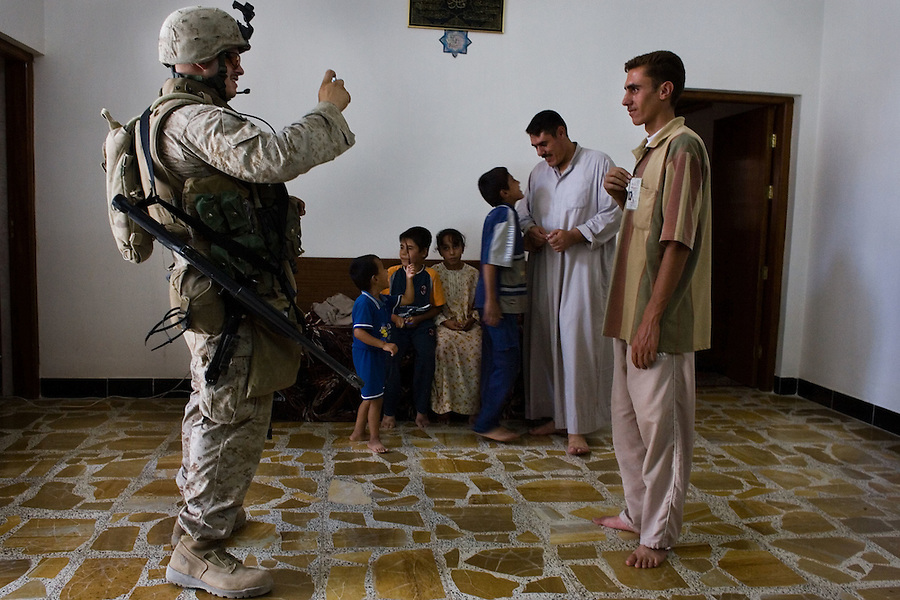 A Marine with Alpha Co. 1st Battalion 6th Marines photographs an Iraqi man during a &quot;census&quot; patrol in Ramadi, Iraq on Fri. Oct. 13, 2006.<br />