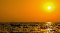 Fine Art Print Photograph, Sunset in Banderas Bay, Puerto Vallarta, Mexico. Fisherman in their small fishing boat sail by in as the warm golden rays of the sun cast highlights and textures on the ocean waters.