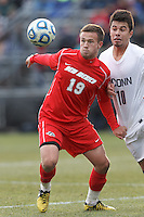 University of New Mexico defender Ben McKendry (19) attempts to control the ball as University of Connecticut midfielder Carlos Alvarez (10) pressures..NCAA Tournament. With a goal in the second overtime, University of Connecticut (white) defeated University of New Mexico (red), 2-1, at Morrone Stadium at University of Connecticut on November 25, 2012.
