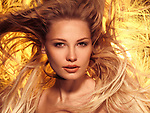 Beauty portrait of a young woman with beautiful brightly lit flying golden hair