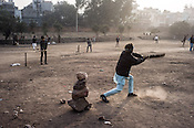 Many young boys cricket sharing a small dusty ground outside the Jama Masjid mosque in Meena Bazaar in Old Delhi, India.