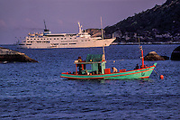 Elements of 2 worlds, a traditional Thai fishing boat and modern cruise ship share an anchorage. Similan Islands Marine National Park, Thailand, Andaman Sea