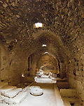 The kitchen chamber at Karak Castle, with the original fireplace and cistern at the end and two grinding wheels on the floor.  The Crusader castle at Karak guarded the eastern border of the Kingdom of Jerusalem after the first Crusade. © Rick Collier
