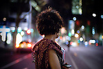 Young woman standing on street in urban environment at night