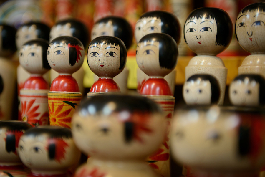 """""""Kokeshi"""" wooden dolls on sale in a shop. Ginzan Onsen, Yamagata Prefecture, Japan, April 12, 2016. Once a sliver-mining town, Ginzan Onsen in Yamagata Prefecture is now one of Japan's best-known and most picturesque hot spring resorts. Its Taisho-period architecture and retro atmosphere is said to have been an inspiration for Hayao Miyazaki's Oscar-winning animated film, Spirited Away."""
