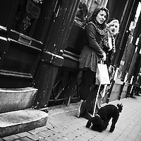 Two stylishly dressed women with dog standing in front of a shop window in central Amsterdam