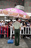 China. Shanghai. World Expo. Expo 2010 Shanghai China.  A policeman stands in front of a line of chinese tourists waiting to enter the Switzerland Pavilion. Pink ice cream sunshade with drawings and chinese writings used for advertisements. White glove and cap. The interactive, intelligent facade enveloping the swiss pavilion is a curtain of woven aluminium elements under which visitors pass to access the urban area on the ground floor of the building. LED lights comprised of an energy source, a storage unit and a consuming unit are incorporated into the facade. The energy produced is made visible in the form of flashes that are triggered by the pavilion surroundings, such as the sun or flashes made by visitor cameras. Thanks to the storage of energy in each individual cell, the facade is also active at night, when the cells will trigger each other.27.06.10  &copy; 2010 Didier Ruef