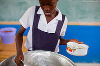 A girl serves rice to her classmates at a public school on July 7, 2010 in Port-au-Prince, Haiti. Most schools in Port-au-Prince didn't open until April, three months after the earthquake.
