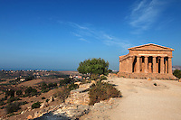 General view of the Temple of Concord, 5th century BC, and surrounding landscape, Agrigento, Sicily, Italy,  pictured on September 12, 2009, in the morning. Well preserved owing to its 6th century AD conversion to a church, the Temple of Concord is a typical example of optical correction whose tapering columns create the illusion of a perfectly aligned building. Its frieze consists of alternating triglyphs and metopes, and the pediment is undecorated. The Valley of the Temples is a UNESCO World Heritage Site. Picture by Manuel Cohen.
