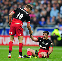 Brad Barritt of Saracens is helped to his feet by team-mate Owen Farrell. European Rugby Champions Cup Final, between Saracens and Racing 92 on May 14, 2016 at the Grand Stade de Lyon in Lyon, France. Photo by: Patrick Khachfe / Onside Images