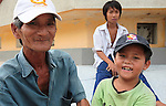 Nguyen Van Dong, 62, a former Viet Cong soldier, poses for a portrait with his grandson at the base of the Giant Seated Buddha at Long Son Pagoda in Nha Trang, Vietnam. The boys parents are both in prison for selling drugs, he said.  July 14, 2011.
