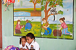 Colombian children in school learning about local wildlife.  Mural behind them depicts people co-existing with Cotton-top tamarins.