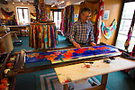 Hugues Beaulieu painting silk scarves in his shop, La Soirie Huo, in the Petit Champlain district of Old Quebec, Quebec, Canada