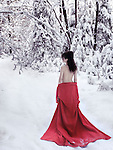 Beautiful half nude woman with bare back in red kimono lowered down to her waist walking away into a snowy winter scenery