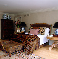 In this master bedroom a large wicker dog basket at the bed's foot  and a fur throw on the bed add a homely atmosphere