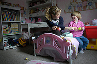 Babysitter Kelly Losure and Jenna Waugh play in Jenna's room while Jenna's mother Kelly Waugh is busy home-schooling her two sons on Jan. 31, 2006. Kelly Waugh says Losure's caregiving has been a big help. Before the family hired a babysitter, Waugh had to juggle Jenna while home-schooling her sons every day of the week. .